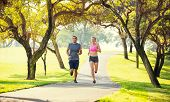 Athletic couple running together. Sport runners jogging on park trail in the early morning.  Healthy