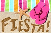 Beach party fiesta travel fun concept. FIESTA written in sand with water next to beach towel, summer sandals and starfish. Summer and sun vacation holidays background.