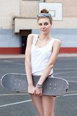 Beautiful  Lady In Jeans Shorts With Skateboard At Sport Court