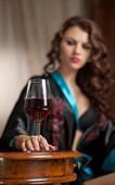 Beautiful sexy woman with glass of wine sitting on chair. Portrait of a woman with long curly hair