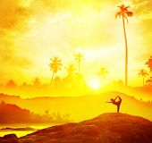 stock photo of natarajasana  - Woman silhouette doing Yoga in tropics near the sea at sunset in India - JPG