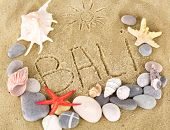 Inscription Bali on wet sand close-up background