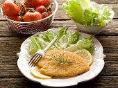 cutlet breaded with salad on dish