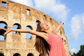 Happy carefree elated travel woman by Colosseum, Rome, Italy with arms raised out and up in ecstatic