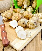 picture of jerusalem artichokes  - One cut and a few whole tubers of Jerusalem artichoke with a bucket a knife and a sacking on a wooden board