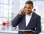Happy black businessman on the phone in modern office lobby.