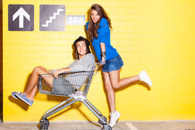 stock photo of jeans skirt  - beautiful long haired girl in jeans mini skirt rides a boy in hat on shopping trolley in front of yellow brick wall - JPG
