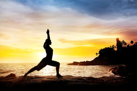 pic of virabhadrasana  - Woman doing Yoga warrior pose in silhouette on the cliff near lighthouse at sunset sky in Kovalam Kerala India - JPG