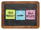 new mindset and new results  concept - colorful sticky notes on a vintage slate blackboard  isolated