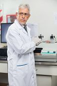 Mature male scientist standing by analyzer in medical laboratory