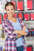 Portrait of confident female customer with arms crossed standing in hardware store