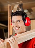 Portrait of happy young carpenter carrying wooden plank on shoulder in workshop