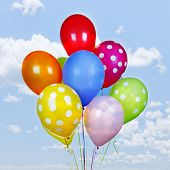 foto of helium  - Colorful helium balloons on blue sky with clouds - JPG