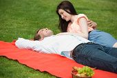 Happy romantic couple lying on blanket and enjoying picnic in a park