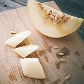 picture of honeydew melon  - Slices of honeydew melon on gray wooden table.