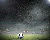 Rain pouring on stadium and soccer ball on grass