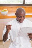 Happy man in bathrobe reading newspaper at home in the kitchen
