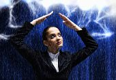 Young businesswoman protecting her head from rain with hands