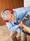 Senior carpenter wearing ear protectors while shaving wood with electric planer in workshop