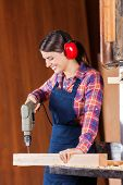 Young female carpenter using drill machine on wood in workshop