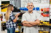Portrait of confident senior man standing arms crossed with daughter in background at hardware store