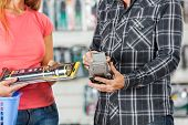 Midsection of couple paying for flashlight through smartphone in hardware store
