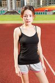 Female Athelete Standing Relaxed On Sports Field Looking At Camera