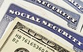 pic of social-security  - Closeup detail of several Social Security Cards and cash representing finances and retirement - JPG