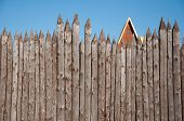 stock photo of log fence  - The wooden fence of sharpened logs timber