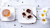 Fresh toasts with homemade butter and blackcurrant jam on wooden background