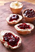 Fresh bread with homemade butter and blackcurrant jam on wooden background