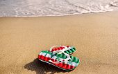 Slippers With The Word Italy On Beach Sand - Holidays And Relaxation Concept