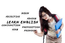 image of verbs  - Female student writes english language materials on whiteboard - JPG