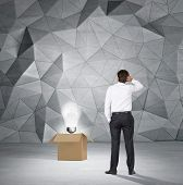 stock photo of lightbulb  - businessman standing and looking to lightbulb in box - JPG