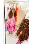 Little African girl try on dress before mirror