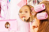 foto of turn-up  - Cute girl making up her face and reflecting in round mirror while sitting turned back with accessories on background - JPG