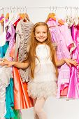 Small cute girl standing between hangers in shop