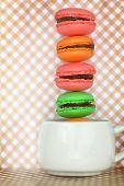 Traditional french colorful macaroons in cup on retro background