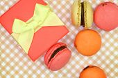 Traditional french colorful macaroons with gift box on retro background