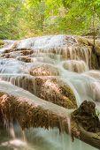 A stream flowing through foggy Autumn woodland at Erawan falls in Thailand National park