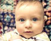 image of candid  - Portrait of playful baby with blue eyes  - JPG