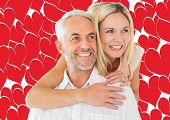 Happy man giving his partner a piggy back against valentines day pattern