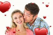 Handsome man kissing girlfriend on cheek against hearts