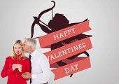 Handsome man giving his wife a kiss on cheek against valentines day greeting