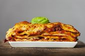 pic of lasagna  - lasagna on a white plate on wood - JPG