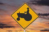 Farmer tractor crossing caution sign with orange sunrise.