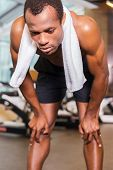 pic of bend over  - Tired young African man with towel over shoulders leaning at his knees while standing in gym - JPG
