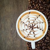 A Cup Of Coffee With Latte Art And Coffee Bean On Wooden Background