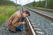 Man Sits On Railway With Magnifier In Hand