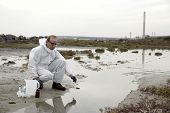 foto of smog  - Worker in a protective suit examining pollution in the water at the industry - JPG
